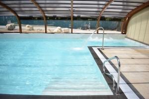 piscine chauffée couverte avec jacuzzi et cascade au bord de la rivière Dordogne dans le Périgord noir proche de sarlat