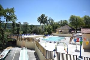 parc aquatique avec aire de jeux aquatique, piscines chauffées et couverte dominé par ses toboggans en bordure de la rivière Dordogne dans le Périgord noir